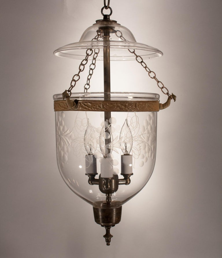 A lovely hand blown glass bell jar lantern from England with an etched vine motif. This petite, circa 1860 pendant is accented with its original brass band and finial candleholder base—hard to find in a 150 year-old lantern. The period smoke lid