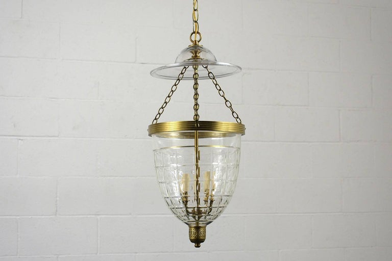 This 1980s Regency-style pendant lantern has a cut glass shade with a square design and brass accents along the top and bottom. Inside the shade are four lights with faux candle covers. The chain is 12 inches long with a glass top shade. This
