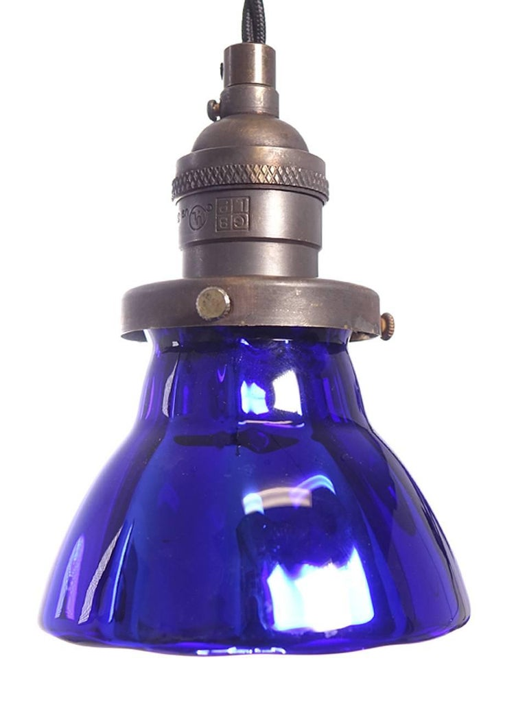 These deep blue pendants are small but striking. They are hollow handblown blue glass that is mirrored inside. It has a subtle panelled shape that nicely catches the light. These are perfect hung in groups. These lamp shades were a short limited