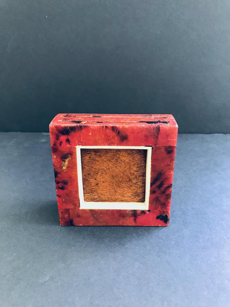 Organic Modern double sided photo frame comprised of exotic handcrafted materials. Petite trapezoid frame features mosaic pen-shell inlays over palmwood. Lacquered and hand-dyed in red and black with bone trim accent. Two top slits fit 2