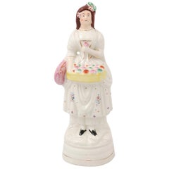 Petite English Porcelain Decorative Object Depicting a Lady with a Floral Basket