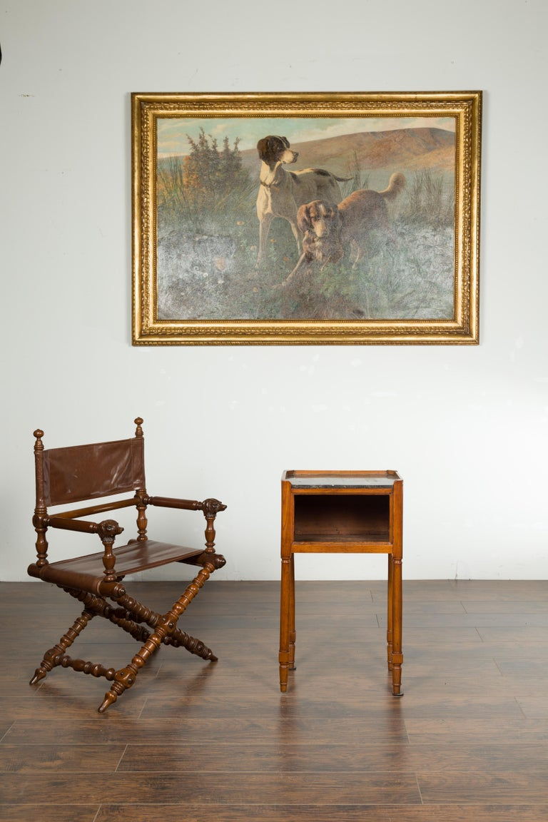 A petite French walnut side table from the 19th century, with marble top and cylindrical legs. Created in France during the 19th century, this petite walnut table features a rectangular black marble top with canted corners surrounded by a