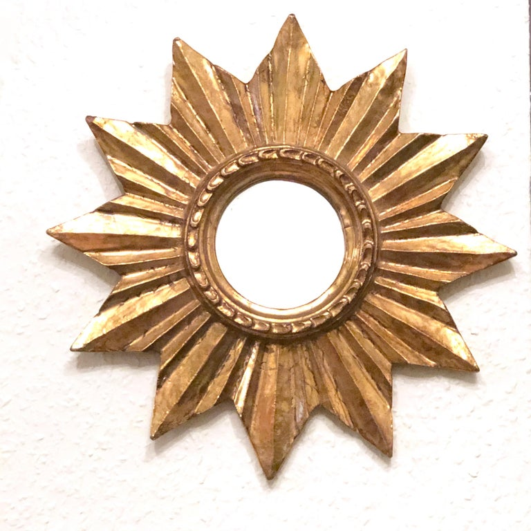 A gorgeous petite starburst mirror. Made of gilded wood. No chips, no cracks, no repairs. It measures approximate 13 1/2