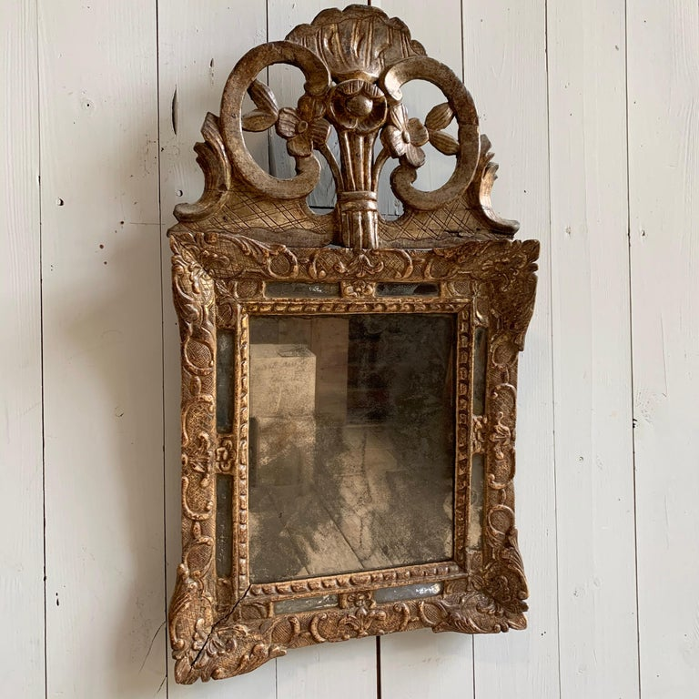 A petite Louis XV period mirror with carved and embossed decoration with an upper crest over a rectangular glass plate, circa 1760, France.