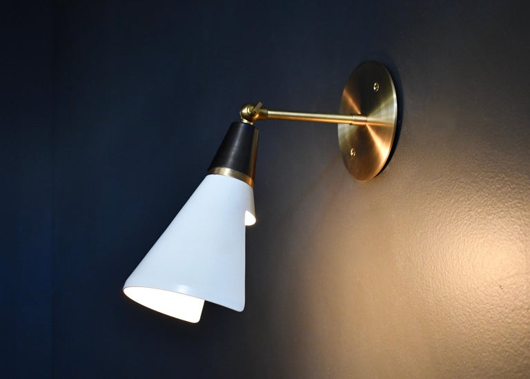 The Petite Magari wall lamp or sconce is handmade to order by Blueprint Lighting. The shade has a swivel mechanism for rotation. This design is strongly influenced by both French and Italian Mid-Century Modernism and features a distinctly beveled