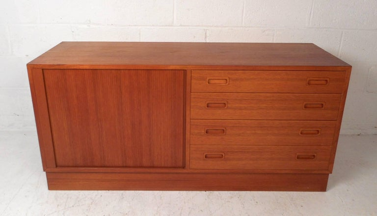 This beautiful vintage modern sideboard features a tambour door that hides a large compartment with two shelves and four large drawers. Sleek design with a blonde colored interior and an elegant teak wood grain throughout. Quality craftsmanship with