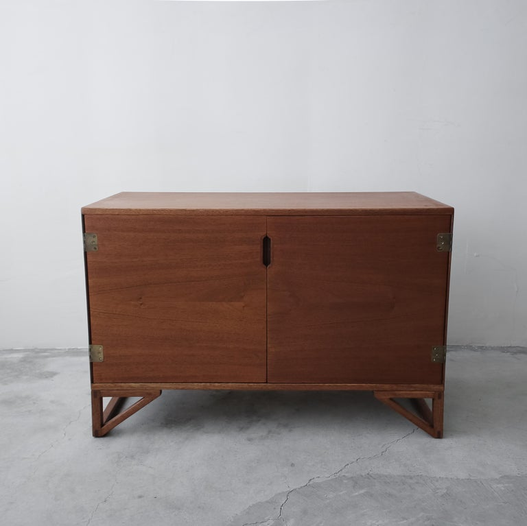 Simple, petite Danish credenza by Svend Langkilde. Simply clean lines and small size make it perfect for and small space that needs a bit of hidden storage.  Credenza is in overall good vintage condition. The back has been painted green and there