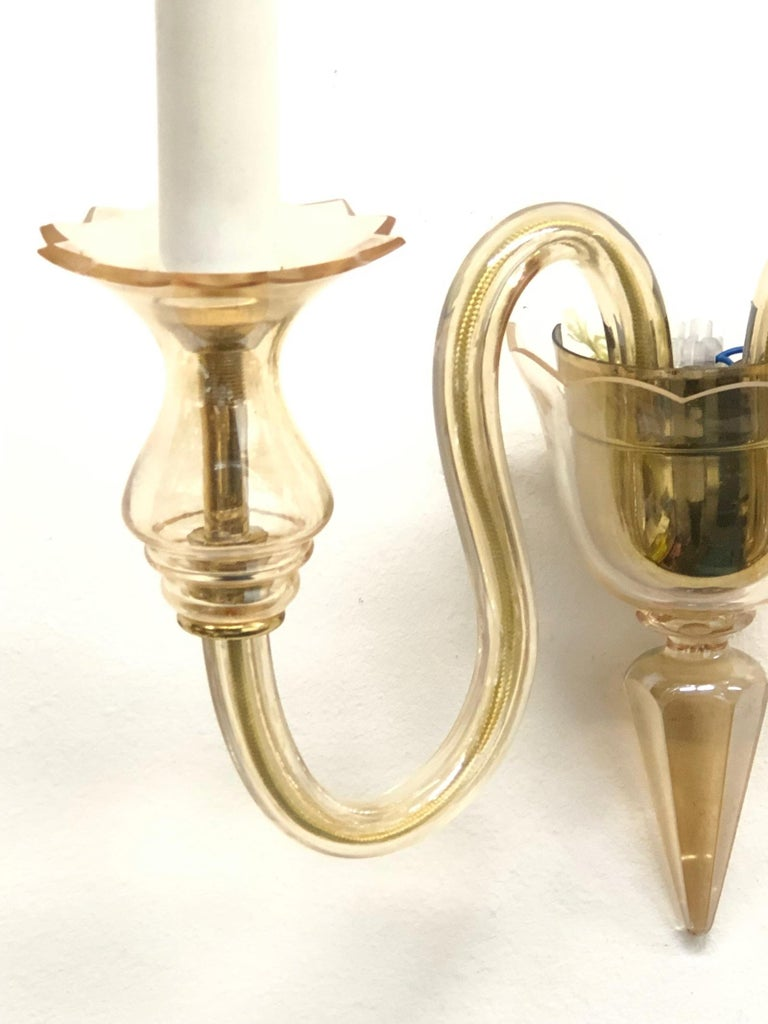 This Hollywood Regency style sconce is made of Murano glass, it has two arms with bulb holders. The fixture requires two European E14 candelabra bulbs, each bulb up to 40 watts. Bulbs are not included in this listing.