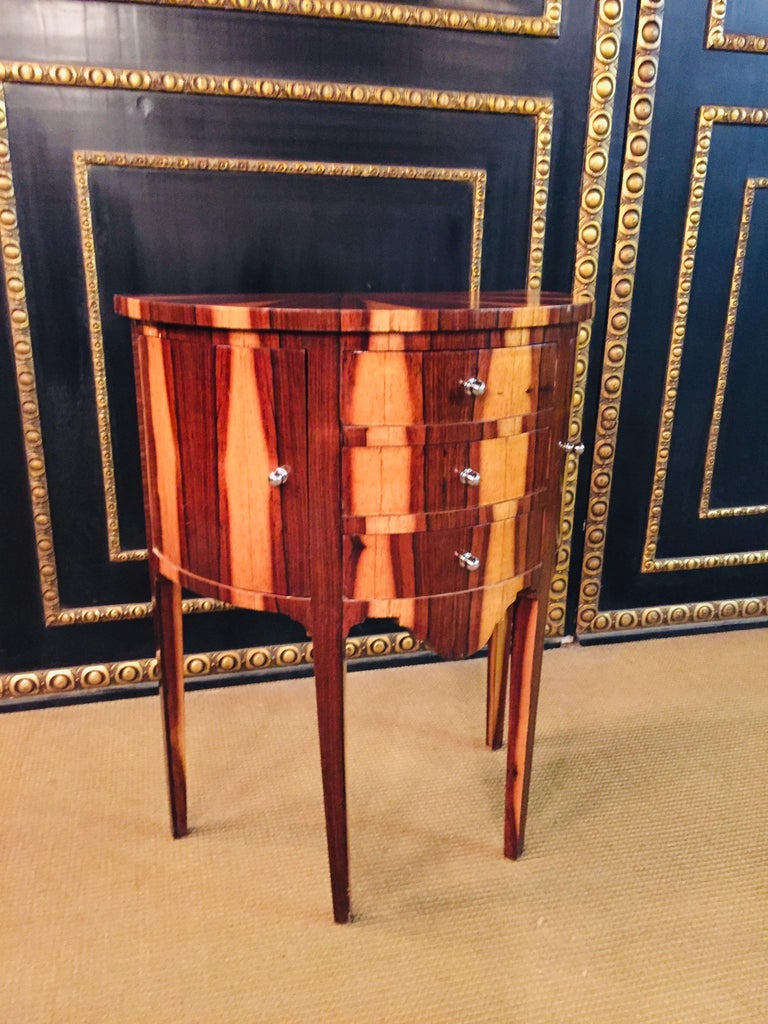 Rosewood, So-called demilune. Semicircular body on conical square legs. With different veneer panels framed by thread and ribbon inlays. The front is dreischübig, flanked by a quarter-round door. Beautiful patina.