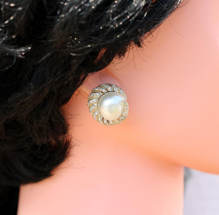 A pair of 18K white gold earrings borrowing design cues from the sea, with a nautilus like style. At the center of each earring is an approximately 15mm large South Sea pearl. Wrapping around the pearls are a combined total of approximately 1.40ct