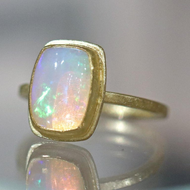 Fiery Ring handcrafted by acclaimed jewelry maker Petra Class featuring a stunning, vibrant 2.25 carat Ethiopian opal cabochon bezel-set in the designer's signature finely-textured 22k yellow gold frame atop an 18k yellow gold squared band. Opal has