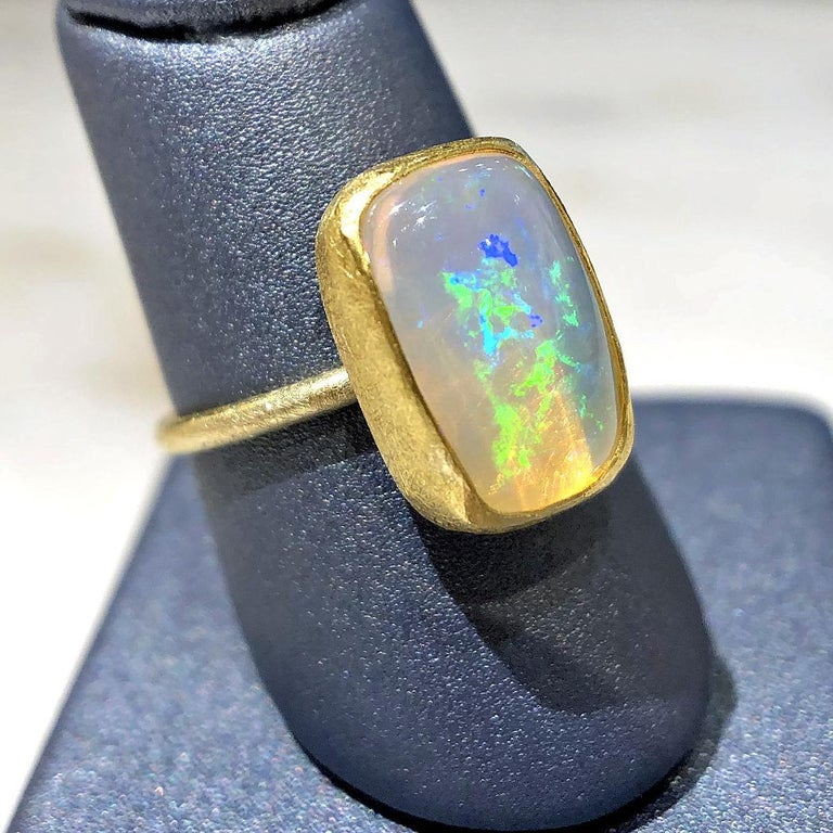 Fiery White Ethiopian Opal Cabochon Ring handcrafted by acclaimed jewelry artist Petra Class featuring a stunning, vibrant opal cabochon bezel-set in the designer's signature finely-textured 22k yellow gold atop an 18k yellow gold band. Size 6.25