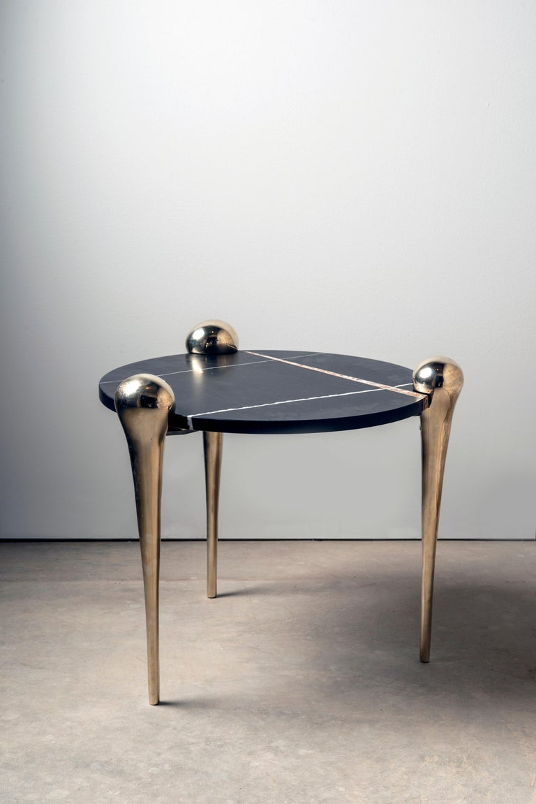 The Petra side table features a honed & enhanced marble tabletop and three sculptural bronze legs. The bronze legs are inspired by the strong yet elegant hind legs of a camel, and are sand-cast at a local Pennsylvania foundry from a hand-shaped