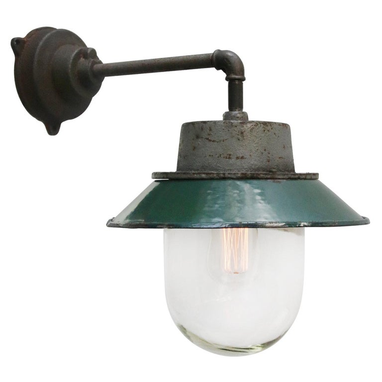 Petrol enamel industrial wall lamp with white interior. Petrol cast iron top, cast iron arm Clear glass   Diameter cast iron wall piece: 12 cm. Three holes to secure.  Weight: 4.00 kg / 8.8 lb  Priced per individual item. All lamps have been