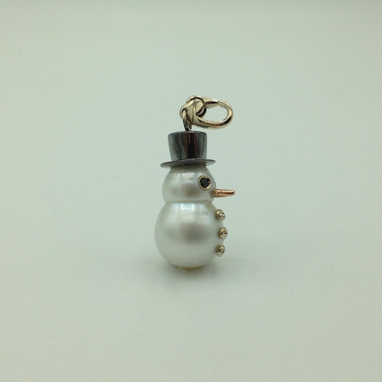 I wanted to create for the winter time a new pendant with an Australian pearl. Its special shape inspired me to create a snowman. It has a cylinder hat  plated black rhodium.  Its eyes are two black diamonds, in total ct 0,03. Its carrot nose is in
