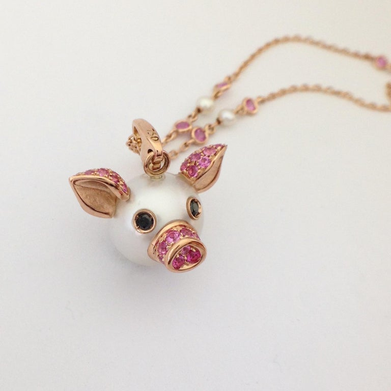 I created a fun pendant / charm using an Australian button pearl (diameter 13.5 mm) that represents the head of a piglet. It is embellished with a pavé of pink sapphires that cover the elements in pink gold: the ears and the nose. The eyes consist