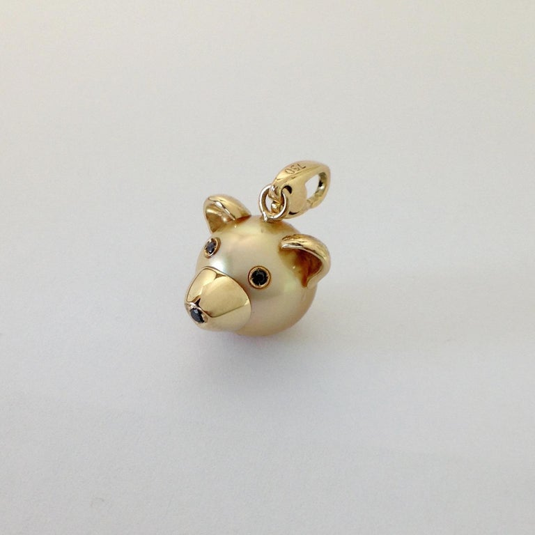 I use a gold Australian pearl to make a little head of a bear. All the particulars are in 18 karat yellow gold.  The eyes and the nose have a black diamond each, they are ct 0,05 in total. The diameter of the pearl is 12 mm. The ring for the