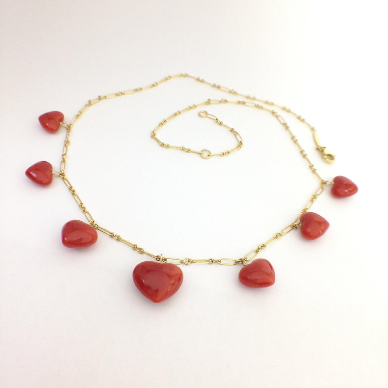 Italian Natural Red Coral Heart Necklace Handmade 18 Karat Gold made in Italy This is a necklace completely handmade in yellow 18Kt gold. It has 7 red coral hearts positioned from smaller to larger towards the center of the necklace. It is 43 cm or