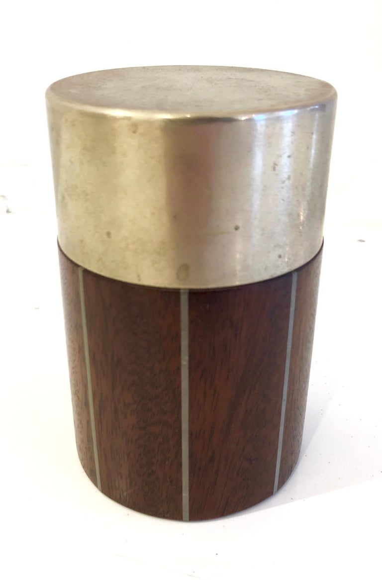 Small canister box of solid cuban mahogany with incised pewter bands and pewter lid. Paul Evans studio label to underside.