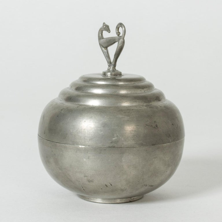 Cool pewter jar by Sylvia Stave, in a smooth, plump shape. A beautifully sculpted, graphic greyhound serves as decoration and knob.