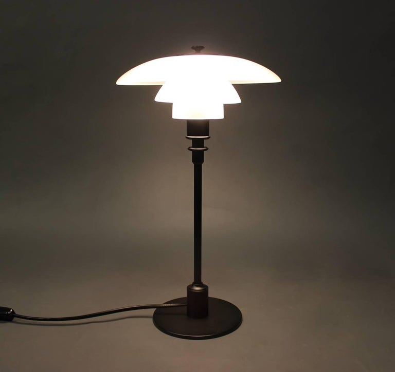 PH 2/1 table lamp, anniversary model, designed by Poul Henningsen and manufactured by Louis Poulsen, 2010s. The lamp is with shades of matte opaline glass and black lacquered frame.