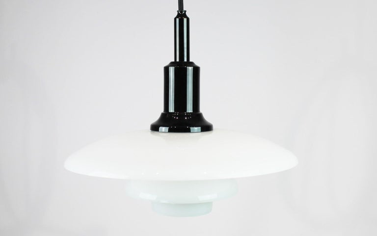 PH 3/2 pendant designed by Poul Henningsen and manufactured by Louis Poulsen. The lamp is of white opaline glass and black chromed.