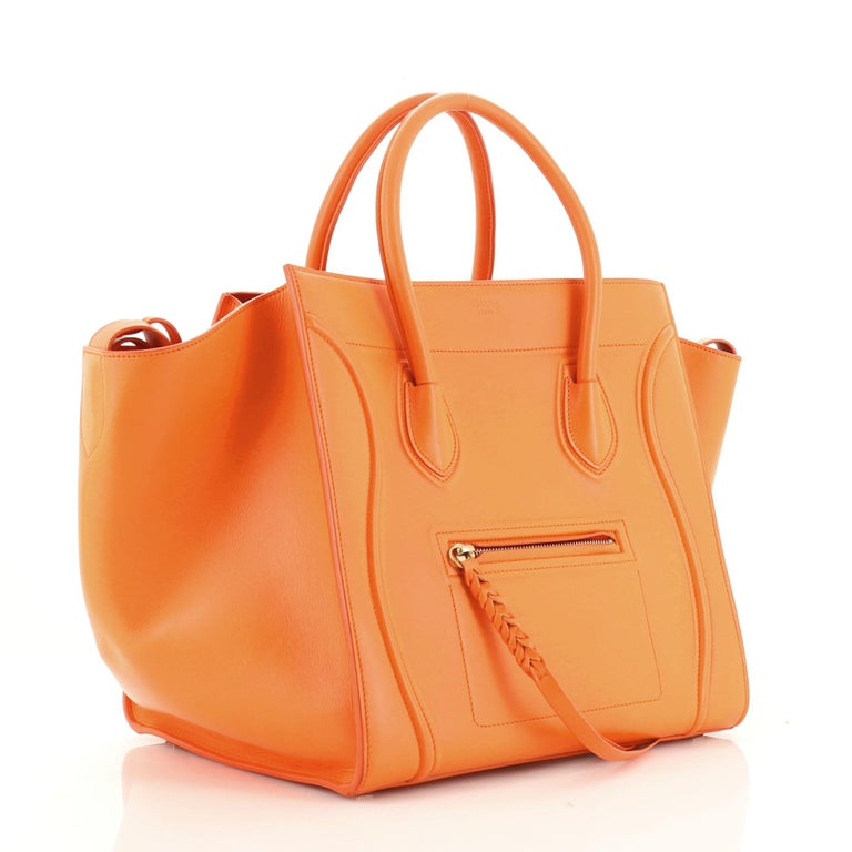This Celine Phantom Bag Smooth Leather Medium, crafted in orange smooth leather, features dual rolled handles, front zip pocket, and aged gold-tone hardware. It opens to an orange suede interior with side zip pocket.   Estimated Retail Price: