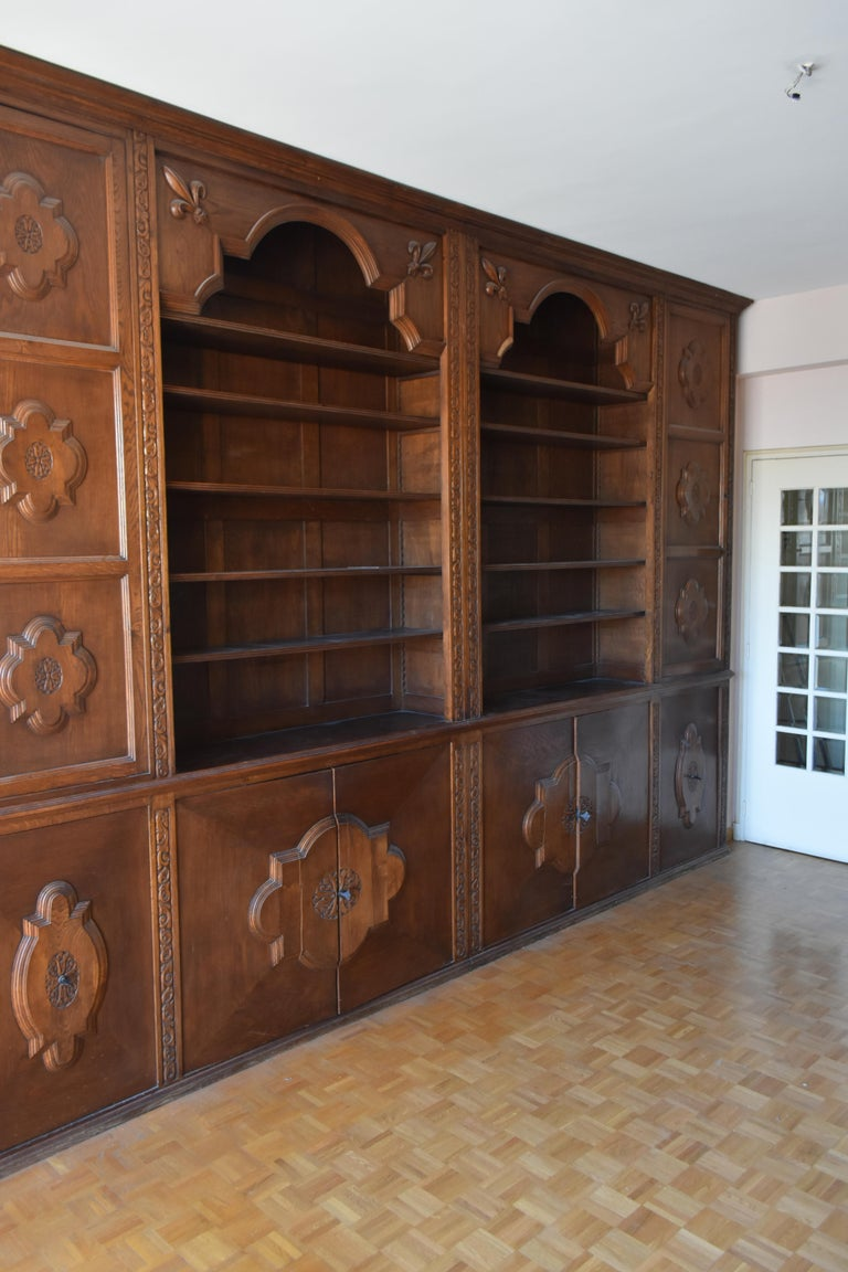 Woodwork forming oak library style 1900s composed of numerous storage and shelves. Originally it was a pharmacy woodwork. Decor with lily flowers.