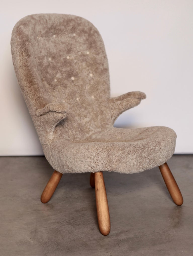 A rare version of the 'clam' easy chair by Philip Arctander, with stained birch legs, armrests, and lambskin upholstery.