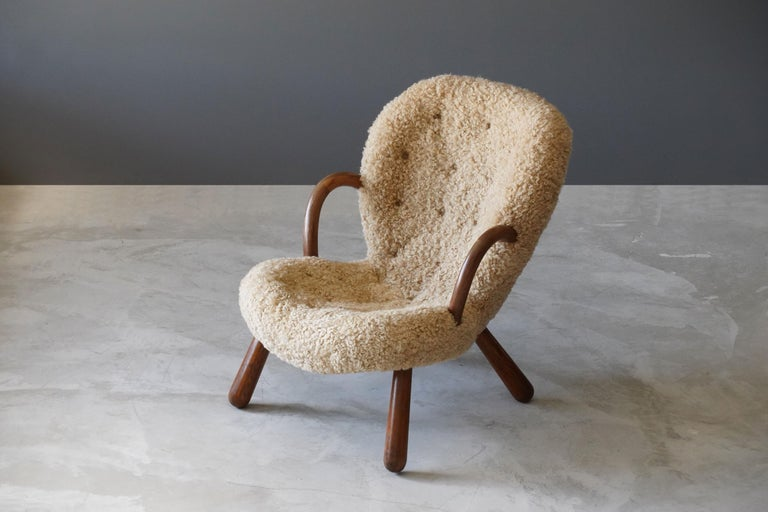 An organic Philip Arctander lounge chair or clam chair. Stained beech and authentic brand new sheepskin upholstery. Designed in 1944 and produced in the late 1940s for Nordisk Staal & Møbel Central.   Other 20th century designers working in the