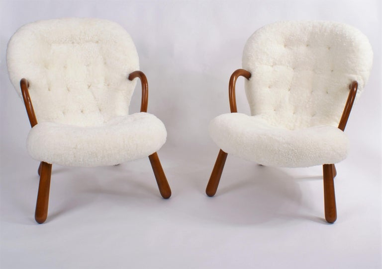 Pair of Philip Arctander 'clam' easy chairs in white sheepskin and legs in stained beech. Buttons in leather. Designed 1944. This pair is from the 1950s.  Price is for the pair.  Single chair is also available. Contact seller for details.
