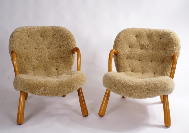 Pair of Philip Arctander 'clam' easy chairs in honey/natural coloured sheepskin and beech legs and armrests. Buttons in natural leather. Designed 1944.