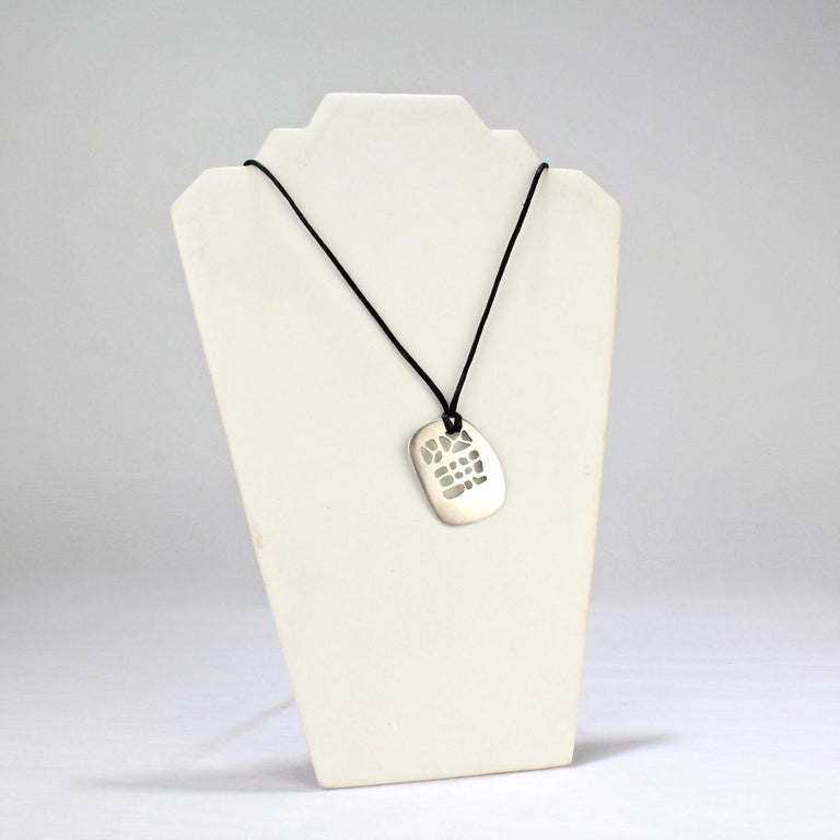 A simple modernist pendant by Philip Morton in sterling silver.  Of slightly convex tablet form with organic pierced openings suspended by a later associated black cord.  Philip Morton was a founding member of SNAG, the Society of North American