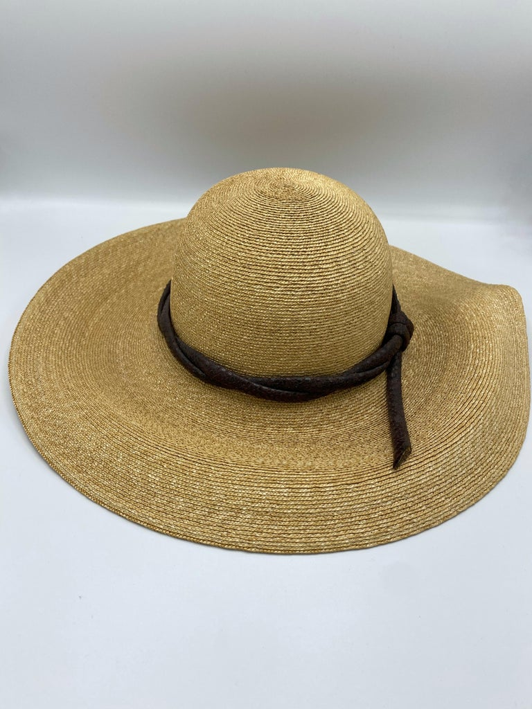 Product details:  100% natural fibers. Featuring light beige color straw hat with brown animal skin leather cord like design detail around. Measurements: 22