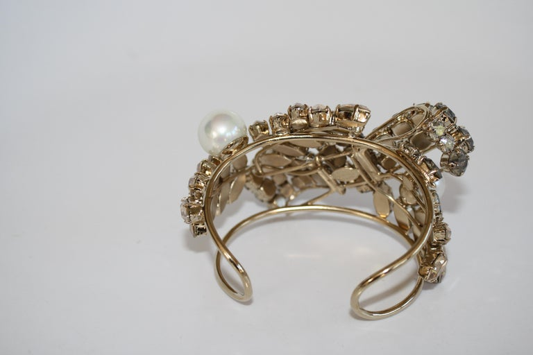 Swarovski Crystal bow and leaf motif cuff bracelet with glass pearls from Philippe Ferrandis. Cuff is malleable and can adjust to wrists both large and small.