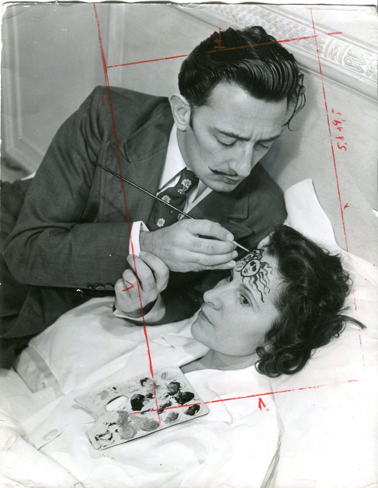 Philippe Halsman Black and White Photograph - Dali is painting medusas head on Galas forehead
