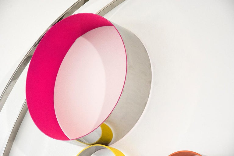 A playful collection of steel rings and disks bubble and swirl within the confines of two steel hoops. The elements of this modernist inspired wall tondo by Philippe Pallafray are polished to a high sheen and patinated in hot pink, lemon and orange.