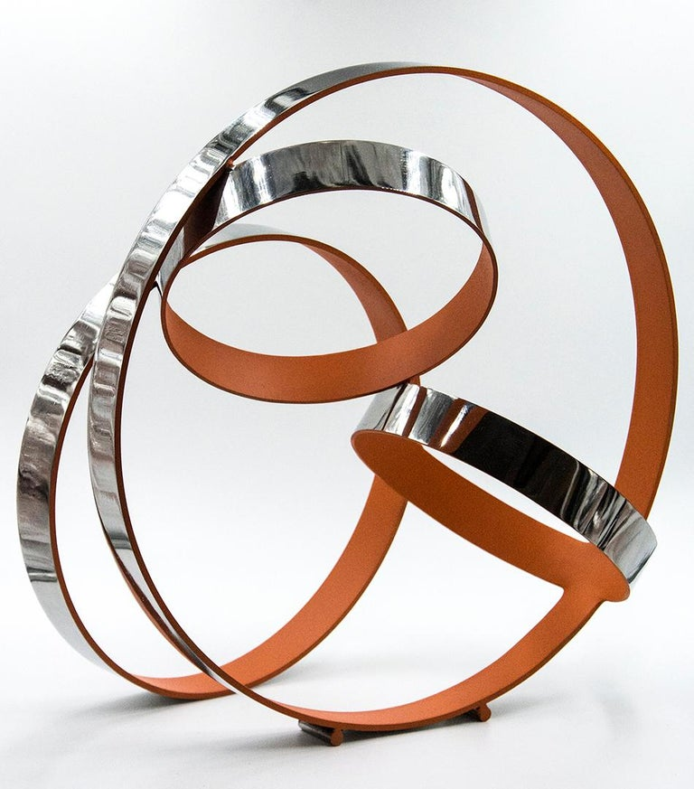 Four stainless steel rings, polished to a sheen on the exterior and dusty orange on the interior, intersect in this playful composition by Philippe Pallafray. This editioned sculpture is number 4/10.  Philippe Pallafray (b. 1965, France) is a member
