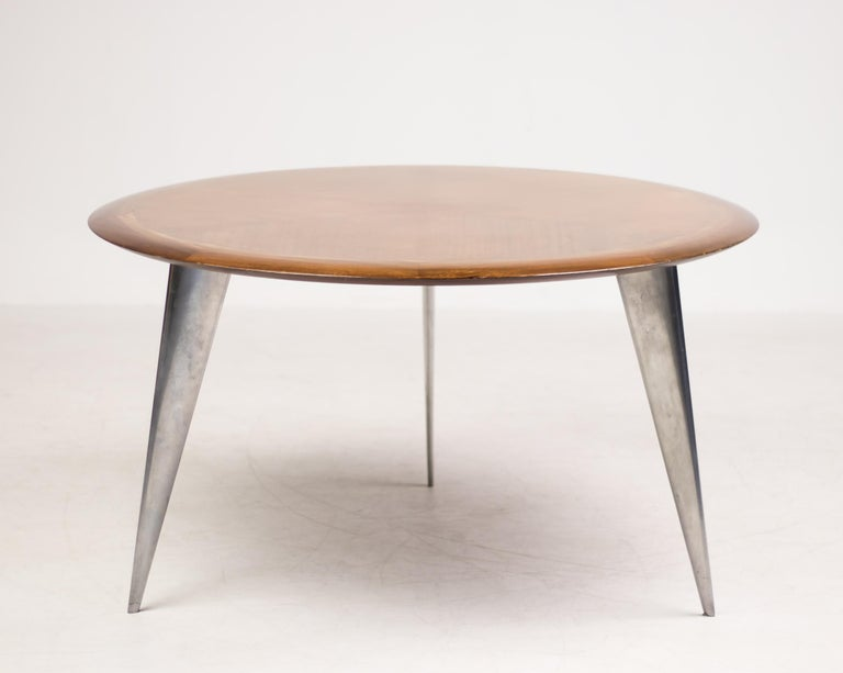 Round dining table in mahogany designed by Philippe Starck in 1987 for Aleph France; a division of Driade. From the limited series Lang, model M. A flying saucer-like sleek bookmatched mahogany veneer top dining table over three sharply angled
