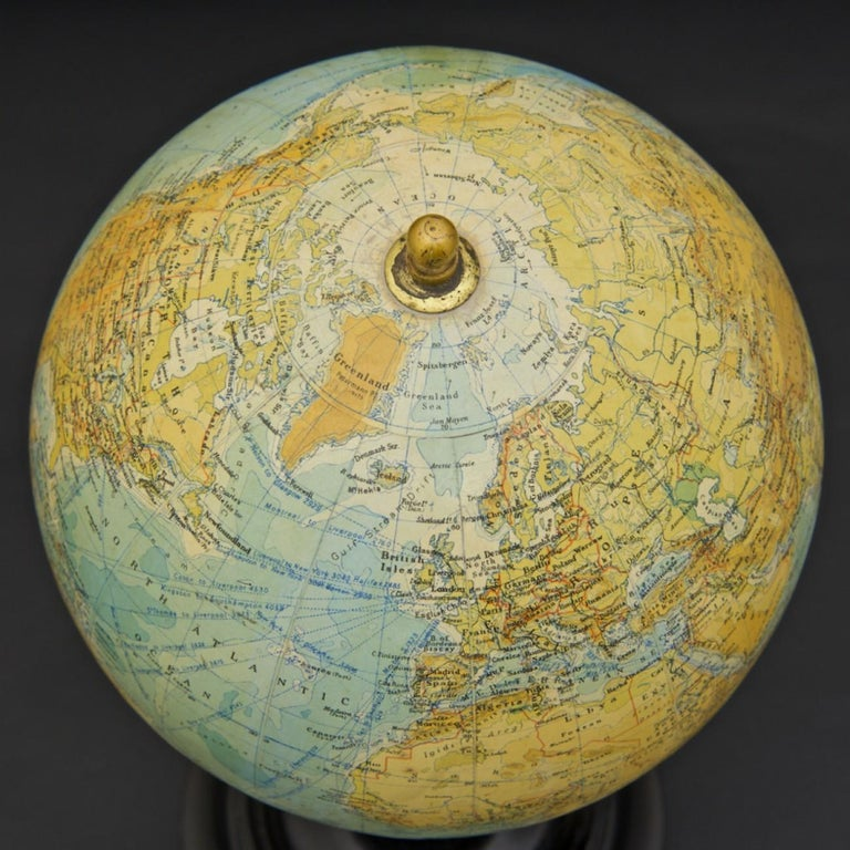 An attractive 9 inch terrestrial globe by George Philip and Son; circa 1925. Printed in several colours and presented on a brass inclined plain mount attached to original turned ebonized wooden base and upright, with axis secured at the top by a