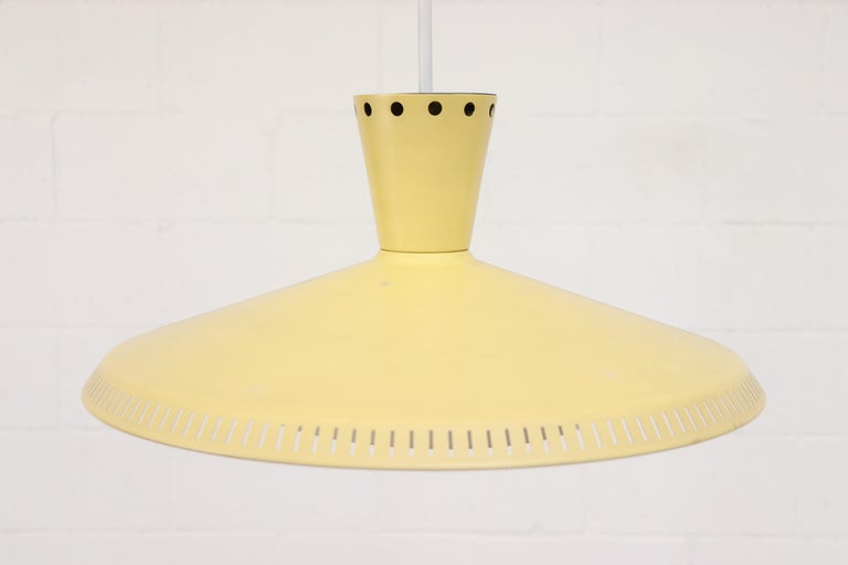 Philips ceiling pendant in pale yellow with Acrylic diffuser. Enameled metal and rectangular slat perforated bottom rim, circular perforated top rim. In original condition with some visible signs of wear consistent with age and use.