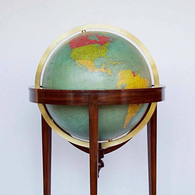 A late 18th century style terrestrial globe printed and manufactured by George Philip & Son Ltd. mahogany and walnut stand, with a paper glass covered compass underneath.