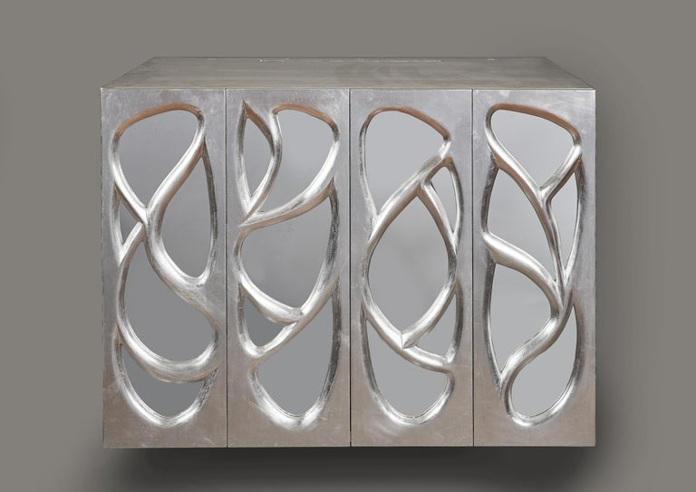 Phillip Lloyd Powell (1919-2008)  A rare and astounding hanging cabinet by Pennsylvania Studio Craft movement master Phillip Lloyd Powell, in sculpted wood covered in silver-leaf with mirrored inserts. With two hinged doors and a single shelf. A