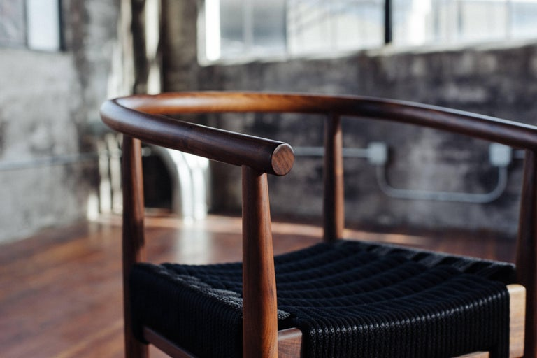 Phloem Studio Captains chair is a modern contemporary take on a classic Captains chair handmade custom to order with turned tapered and shaped legs and a horseshoe shape tube arm and back shaped from solid walnut. Appropriate as both a dining chair