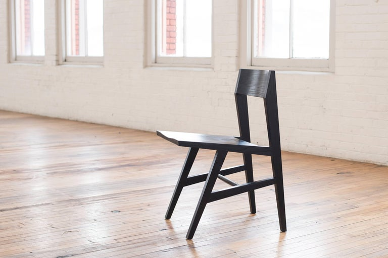 Phloem Studio Jess side chair is a modern contemporary solid wood dining chair in ebonized (black) oak with tapered hardwood legs and a solid wood laminated curved back. The seat has a carved relief for comfort. Appropriate as both a dining chair or