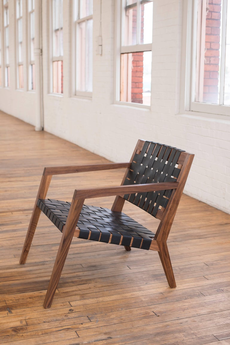 Phloem Studio Nadine lounge chair is a modern contemporary lounge chair with a solid wood walnut frame and a leather strap woven seat. With exposed handcrafted spline joinery and a graceful curved solid wood laminated back. Heavy weight bridle