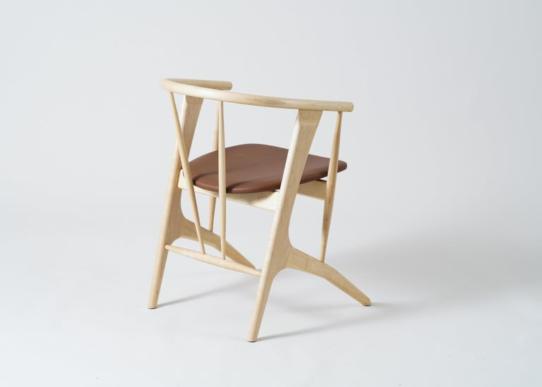 Phloem Studio Zoe chair is a modern contemporary solid wood armchair handmade custom to order with organic flowing shaped legs, spindle bracing, a solid wood steam bent tube backrest with arms and an upholstered seat. Zoe is lightweight and
