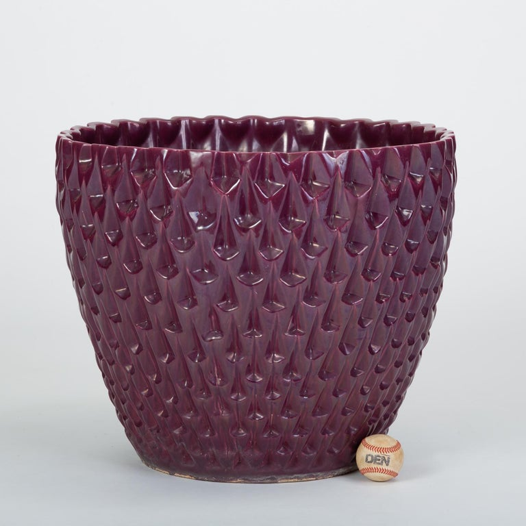 Designed by David Cressey in 1963 as part of the Pro/Artisan stoneware collection for Architectural Pottery, the slipcast Phoenix planter has a bowl shape with an allover geometric relief. This example is has an eggplant purple glaze with a glossy