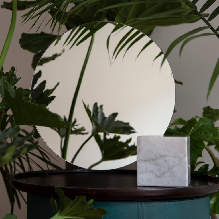 The Pi mirror combines marble and glass to create a playful table mirror that's both delicate and bold. Consisting of a circular mirror cantilevered from a marble base, the minimal form and luxe materials create a sophisticated statement piece that