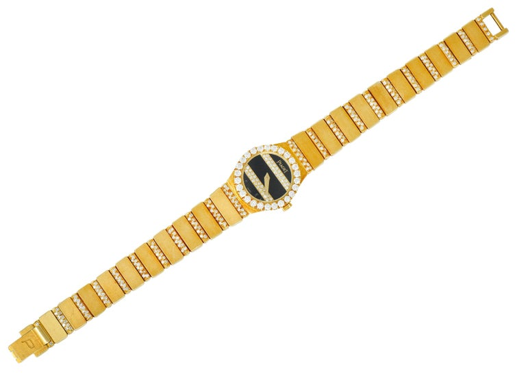 Watch bracelet is comprised of brushed rectangular links alternating with pavè diamond links  Centering a blank onyx face accented by two more rows of pavè diamonds and faceted gold hands  Covered by sapphire crystal and surrounded by a halo of